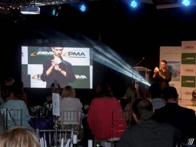Magician Andrew Herring performing on stage at his corporate client's product launch