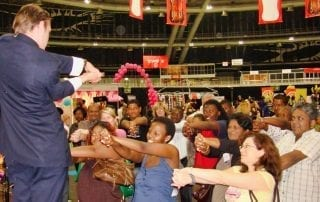 Corporate Magician Marcel Oudejans captivates a crowd at an expo